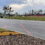 Zdjęcia z przebudowy terenu za szkoła podstawową obrazujące outwardzony teren i wydzielone miejsca parkingowe.